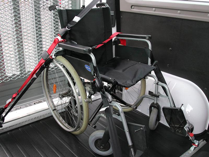 Rollstuhl mit Sicherheitsgurt an speziellen Schienen verankert